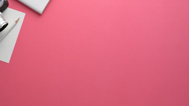 カメラ、文房具、ピンクのテーブルにコピースペースを持つカメラマンワークスペースのオーバーヘッドショット