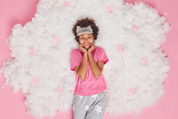 パジャマを着たポジティブな若いアフリカ系アメリカ人女性のオーバーヘッドショットはおはようを楽しんでいます