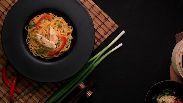 ブラックプレートで提供される野菜と鶏肉のシェズワンヌードルのオーバーヘッドショット