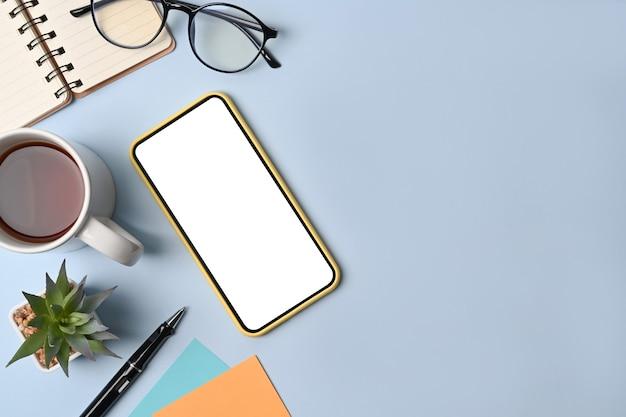 Накладные выстрел из смартфона, очков, чашки кофе и ноутбука на синем фоне.