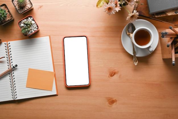 Накладная съемка смартфона с пустым экраном, ноутбуком, чашкой кофе и комнатным растением на деревянном столе.