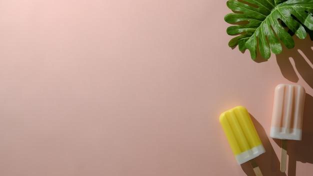 ピンクの背景にイチゴとレモンの味のアイスキャンディーのオーバーヘッドショット