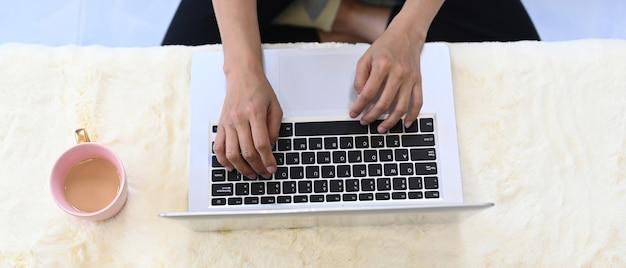 Накладные выстрел из рук молодой женщины, набрав на клавиатуре портативного компьютера на ее рабочем месте.