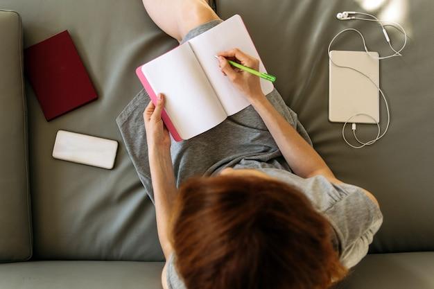 自宅でノートで働く女性のオーバーヘッドショット
