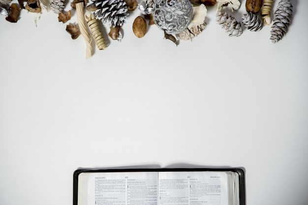 Overhead shot of an open bible on a white surface with pine cones and an ornament on the top