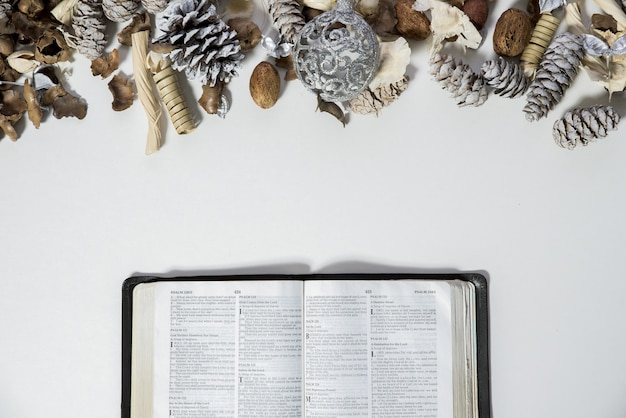 Overhead shot of an opened bible near pine cones and an ornament on a white surface