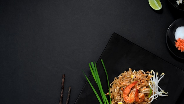 Overhead shot of pad thai, stir fly of thai noodle with shrimp, egg and seasoning in black ceramic plate