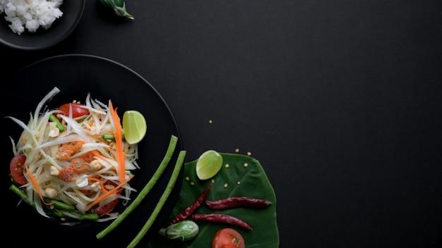 Overhead shot of papaya salad on black plate, ingredients and copy space