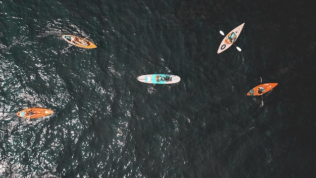 Overhead shot of people in small rowboats in the water