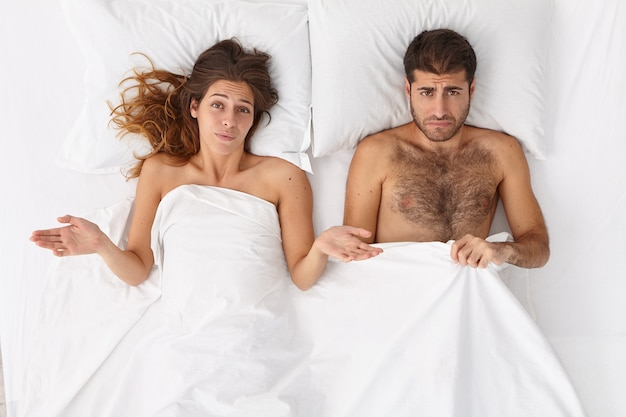 Overhead shot of puzzled woman and her husband have sex problems in bed, displeased expressions, lie under white blanket. man has impotence, erection failure. daylife family troubles concept