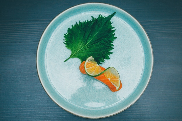 Overhead shot of a salmon sushi decorated with a lime slice and green leaf on a round ceramic plate