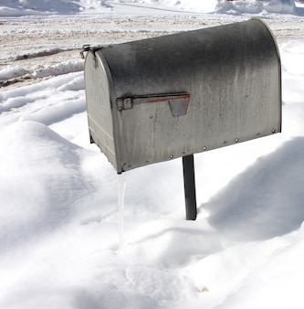 Overhead shot of a silver mailbox with snow in the surface during winter