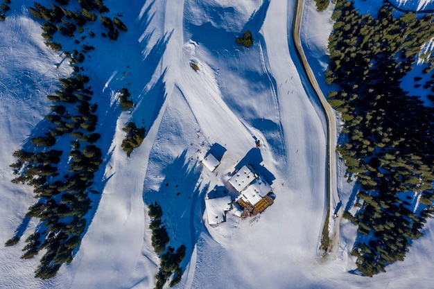 Overhead shot of small houses on a snowy mountain surrounded by trees during daylight