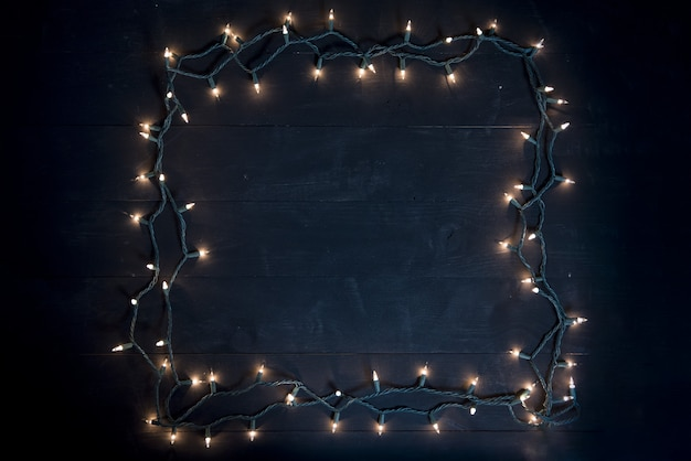 Overhead shot of a square made with christmas lights on a wooden surface