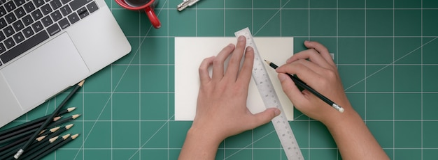 Overhead shot of student cutting paper with cutter on cutting mat