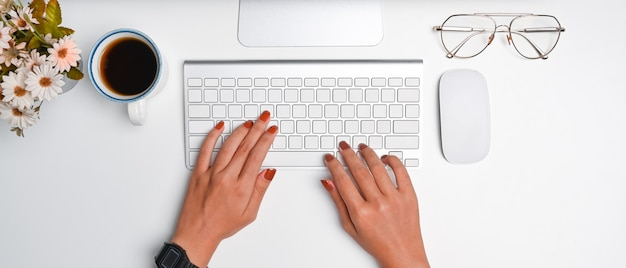 Overhead shot of stylish woman working with computer on white desk.