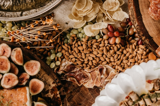 Overhead shot of a table full of almonds, prosciutto, figs, and dry fruit