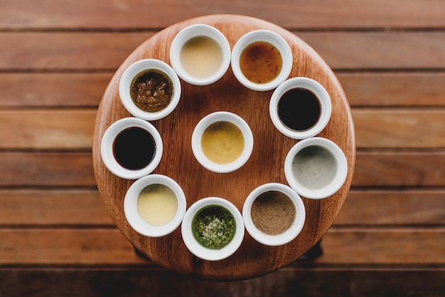 Overhead shot of ten white bowls with different sauces and spices in them aligned on a stool