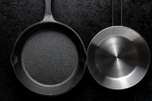 Overhead shot of two metal frying pans on a black background