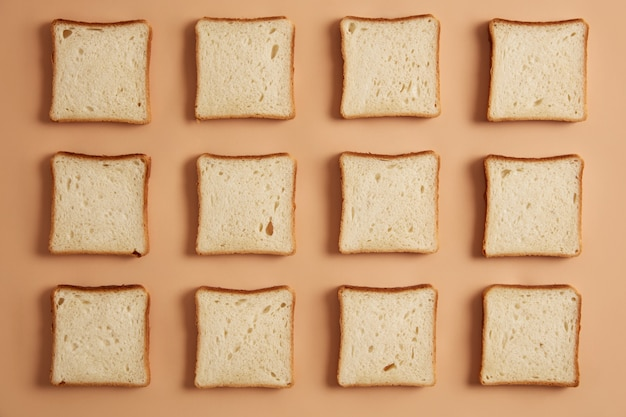 Overhead shot of unroasted bread slices arranged in rows, ready for toasting, isolated on beige studio background. preparing delicious sandwich. tasty snack. sliced bakery product. flat lay.