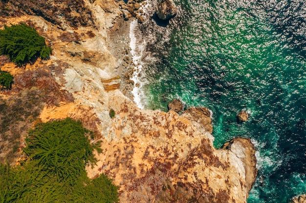 Overhead shot of a wavy sea and rocky coast