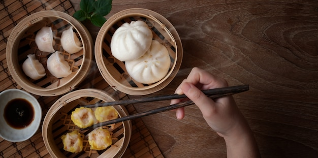 Overhead shot of woman eating chinese steamed dumpling and steamed pork bun in a bamboo steamer
