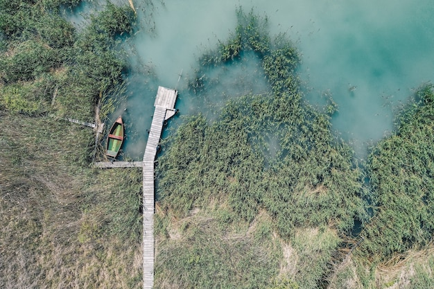 Overhead shot of a wooden dock at the coast with a fishing boat next to it
