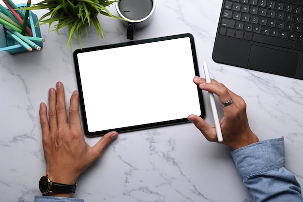 Overhead shot of young man graphic designer holding stylus pen and digital tablet with blank screen on marble table.
