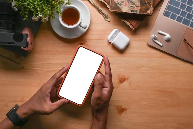 Накладные расходы человека, держащего макет мобильного телефона с пустым экраном на деревянном столе.