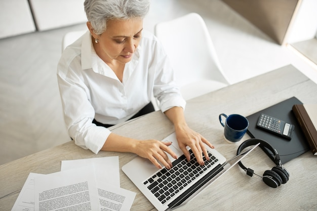 Overhead top view of successful experienced mature female translator or copywriter in formal clothing sitting at office desk with mug, papers, headphones and laptop, typing text