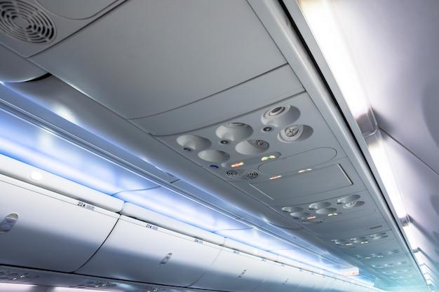 飛行機の手荷物用の荷物ラックと共に頭上の通気口とライト。
