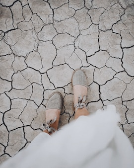 Overhead vertical shot of a female's feet on a cracked ground