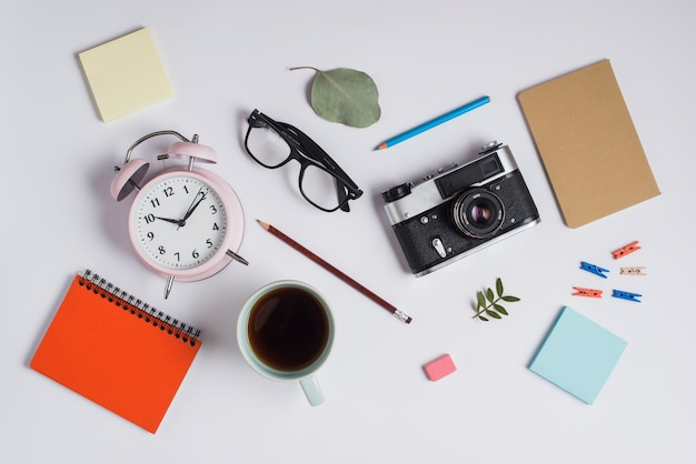 An overhead view of alarm clock; eyeglasses; camera; coffee cup and office supplies on white background