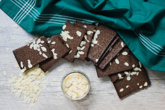 An overhead view of almonds slices and dark chocolate slices on wooden background