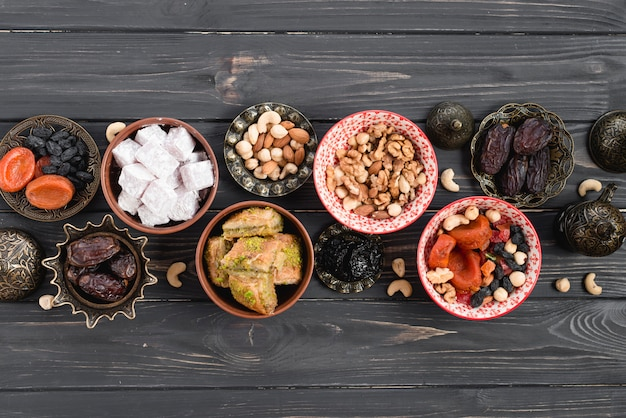 An overhead view of arabian sweets and dried fruits for ramadan on black wooden desk