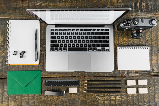 Overhead view of arranged office stationeries and laptop; retro camera on wooden desk