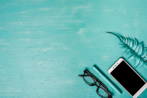 An overhead view of artificial fern leaf; smartphone; pen and eyeglasses on turquoise background