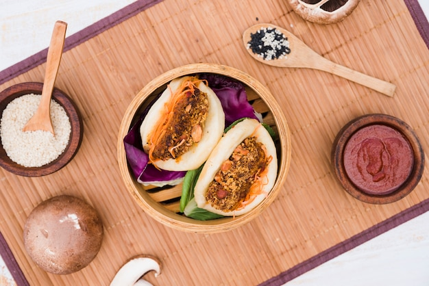 An overhead view of asian sandwich steamed gua bao buns in steamer on placemat