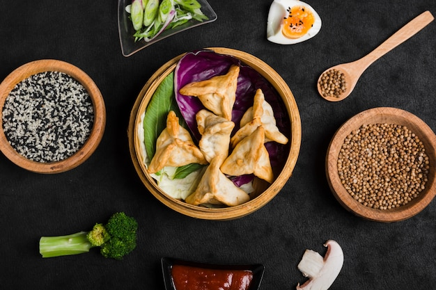 An overhead view of asian style dumplings with sesame and coriander seeds on black background