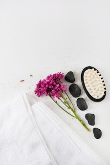 An overhead view of aster flowers; towel; spa stone and massage brush on salt over white background