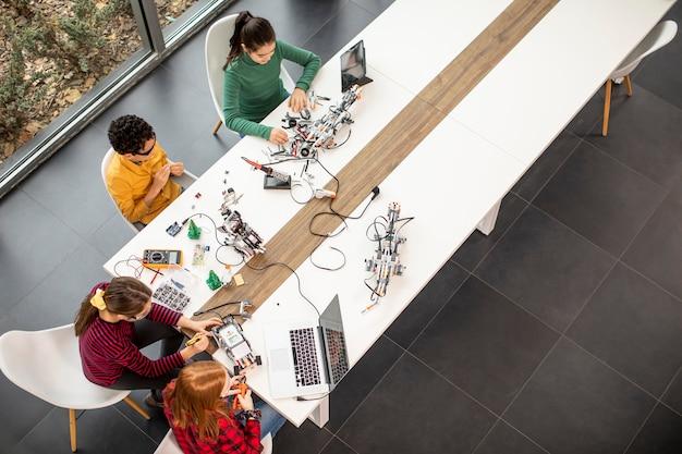 ロボット工学の教室で電気玩具とロボットをプログラミングする幸せな子供たちのグループの俯瞰図