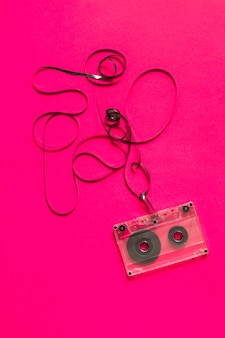An overhead view of audio cassette with tangled tape on pink background