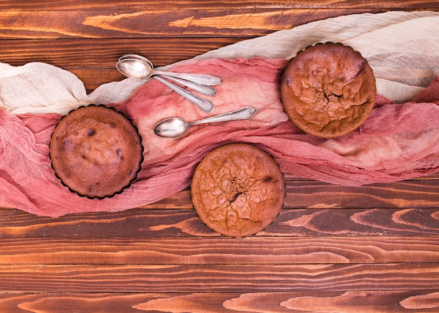 An overhead view of baked chocolate cakes with spoon and clothes on wooden backdrop