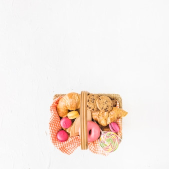 An overhead view of baked and sweet food in the basket over the white background