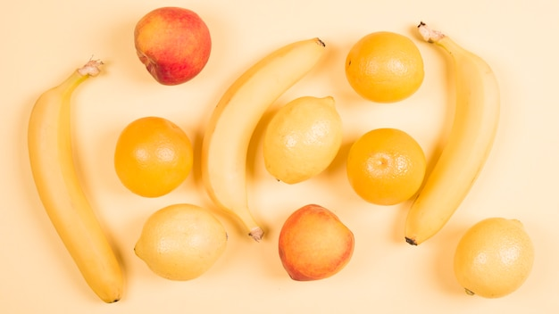 An overhead view of banana; peach; apple; oranges and lemons against beige background