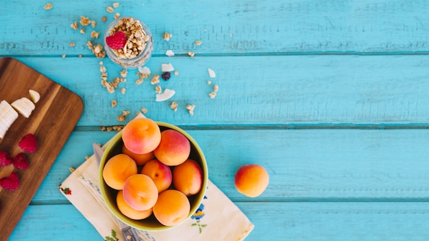 Overhead view of banana slices; strawberries; peach and oats on blue wooden table top