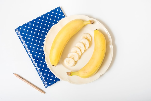 Overhead view of bananas; pencil and notebook on white surface