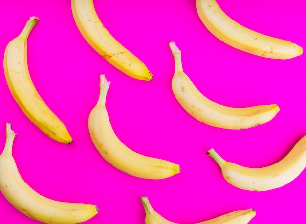An overhead view of bananas on pink backdrop