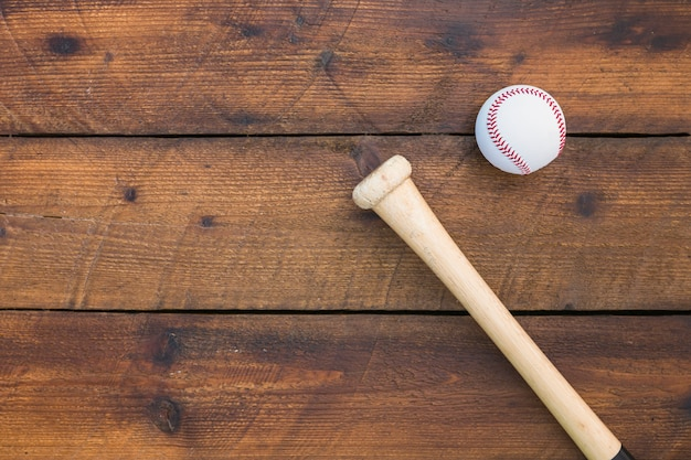 An overhead view of baseball bat and ball on wooden table
