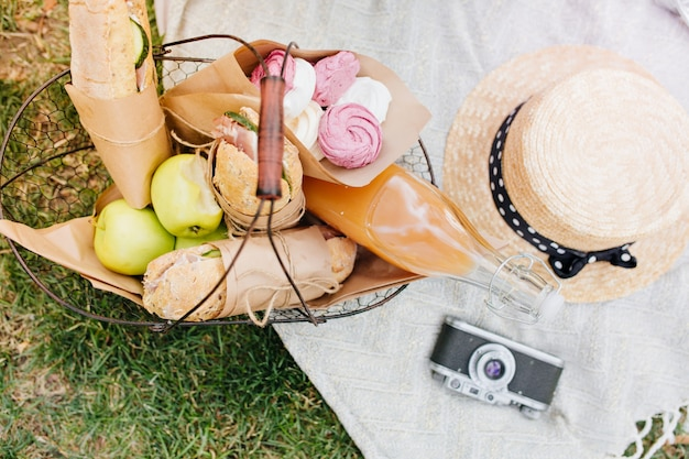 Overhead view of basket with apples, bread and bottle of orange juice. photo from above of food for lunch, camera and straw hat lying on white blanket on grass.